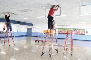 Man installing Litetronics LED Magnetic Retrofits in a middle school.